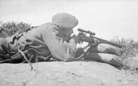 A British sniper takes aim through the telescopic sights of his rifle on the range at a sniper training school in France, 27 July 1944.