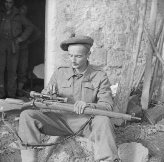 Lance Corporal A P Proctor, a sniper with 56th Division, cleaning his rifle, 24 November 1943.